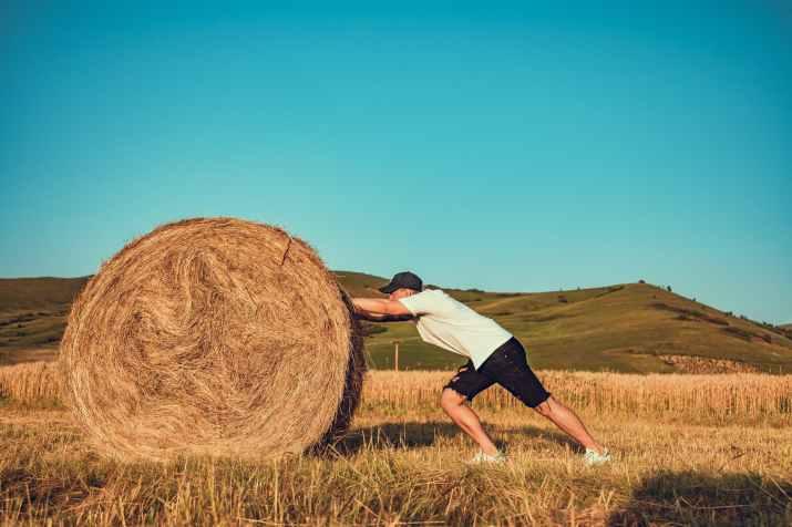 photo of man pushing hay bale